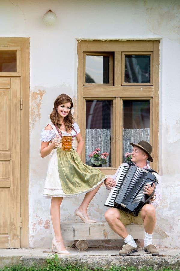 Pares en ropa bávara tradicional con la cerveza y el acordeón foto de archivo