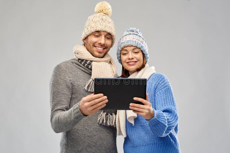 Pares en ropa del invierno con la tableta fotografía de archivo