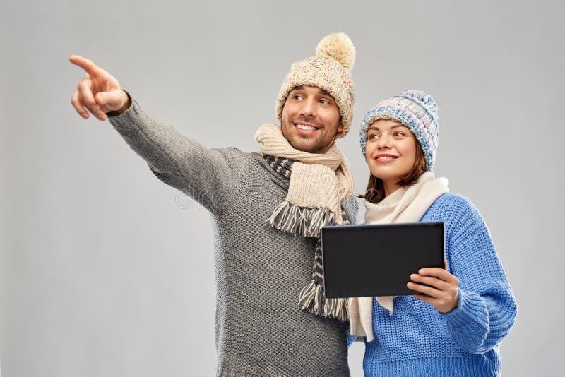 Pares en ropa del invierno con la tableta fotos de archivo