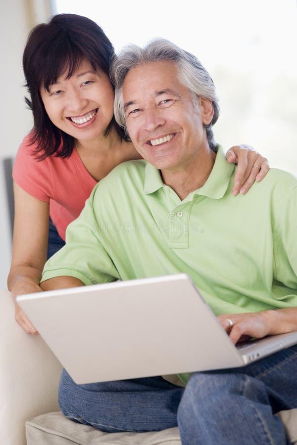 Pares en sala de estar con la sonrisa de la computadora portátil