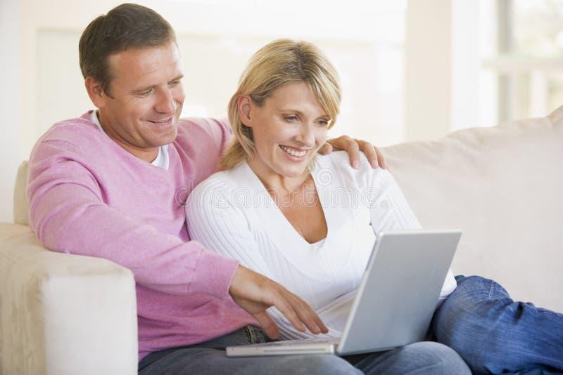 Pares en sala de estar usando la computadora portátil y fotografía de archivo