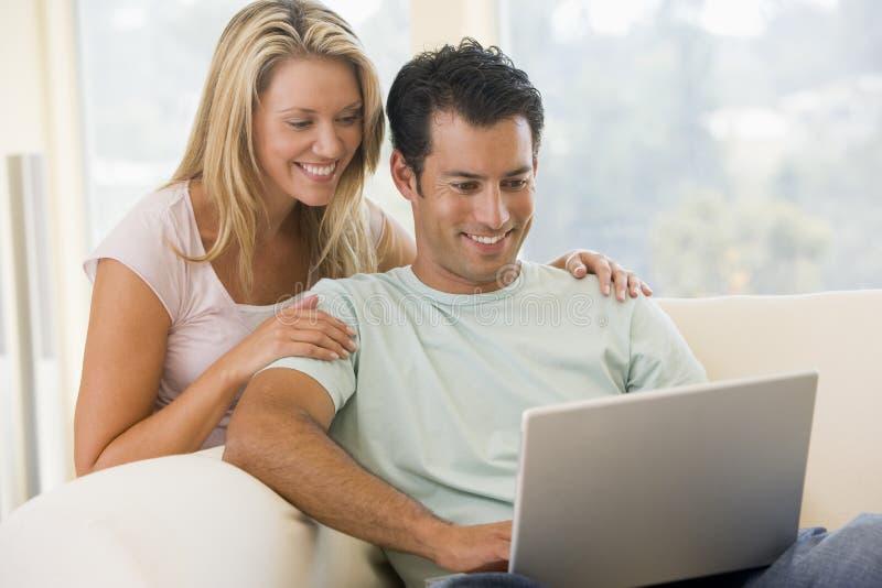 Pares en sala de estar usando la sonrisa de la computadora portátil imagenes de archivo
