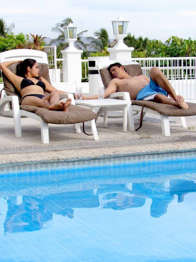 Pares en sillas de salón por la piscina imágenes de archivo libres de regalías