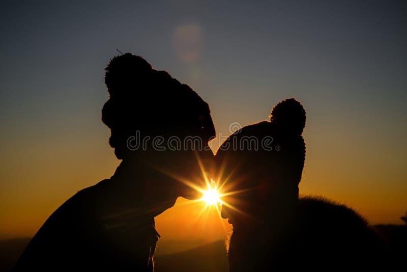 Pares en silueta del contraluz del amor en la colina imagen de archivo