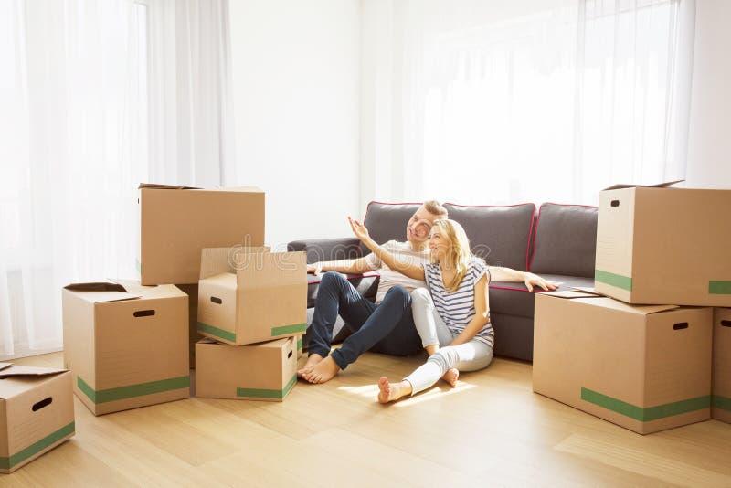 Pares en su nuevo apartamento que se sienta en piso imagen de archivo libre de regalías