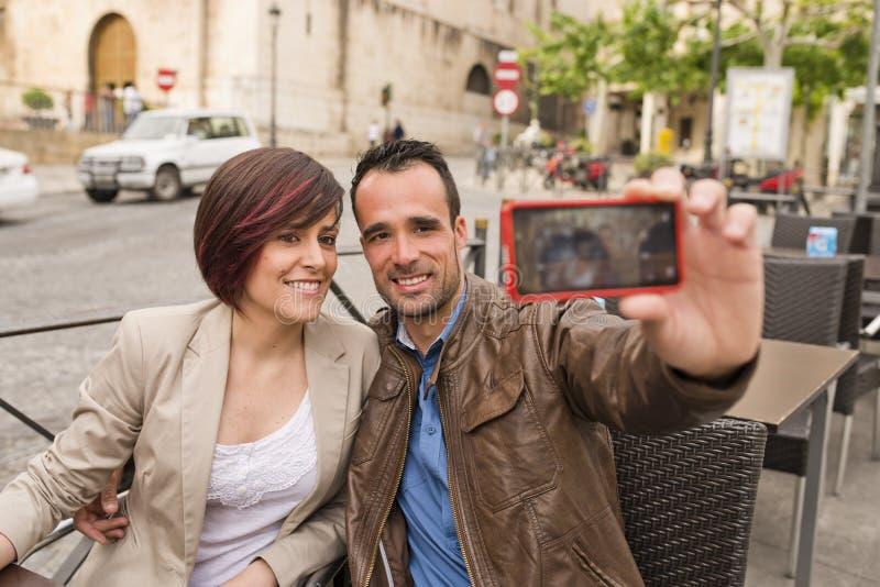 Pares en terraza de la barra del aire libre con el smartphone que toma el selfie foto de archivo libre de regalías