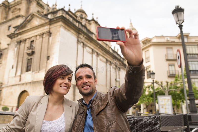 Pares en terraza de la barra del aire libre con el smartphone que toma el selfie fotografía de archivo
