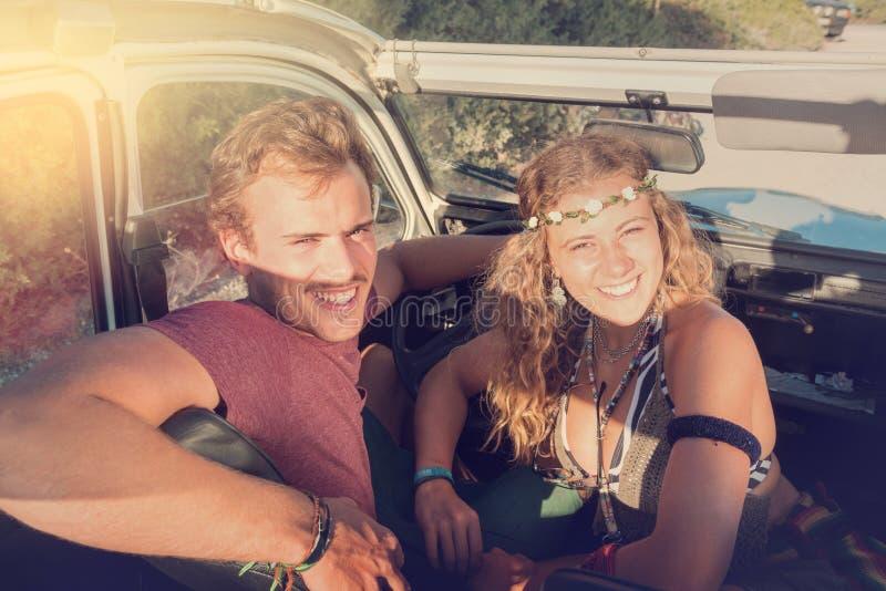Pares en un coche en la puesta del sol fotos de archivo libres de regalías