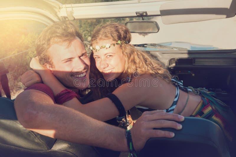 Pares en un coche en la puesta del sol fotografía de archivo libre de regalías