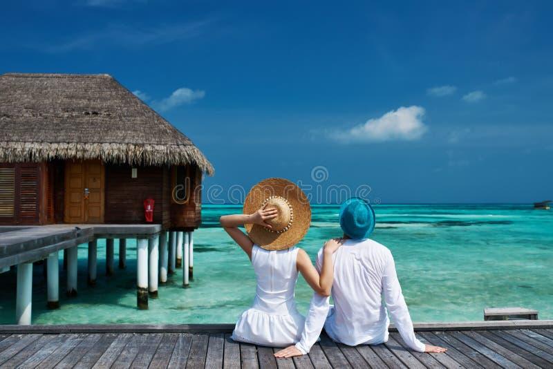Pares en un embarcadero de la playa en Maldivas