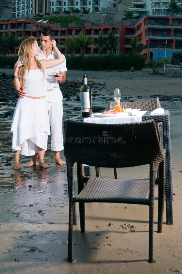 Pares en una cena romántica en la playa imagenes de archivo