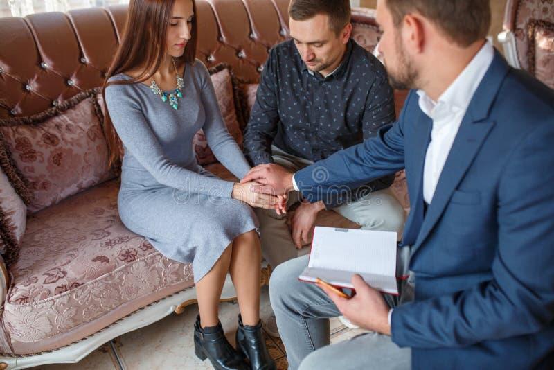 Pares en una recepción con un psicólogo que lleva a cabo las manos que se sientan en un sofá foto de archivo libre de regalías