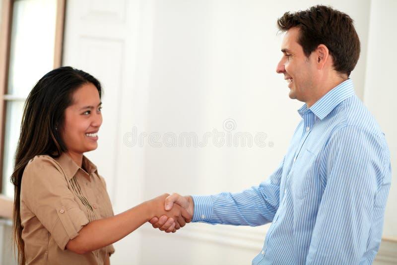 Pares encantadores de los compañeros de trabajo que dan las manos que saludan imagen de archivo