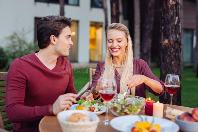 Pares encantados felices que disfrutan de su comida junto imágenes de archivo libres de regalías