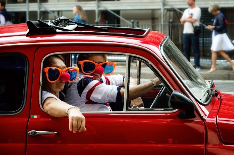 Pares engraçados em um carro do clássico de Fiat 500 foto de stock