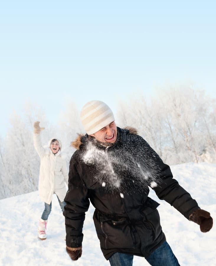 Pares engraçados que jogam snowballs fotografia de stock