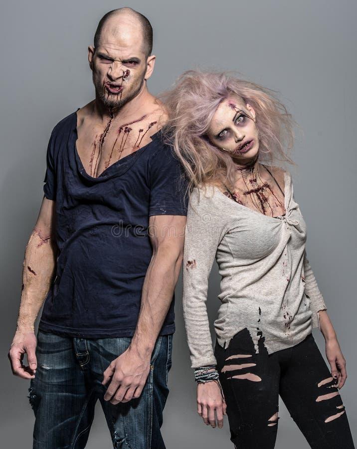 Pares ensanguentados de zombis maus assustadores fotos de stock