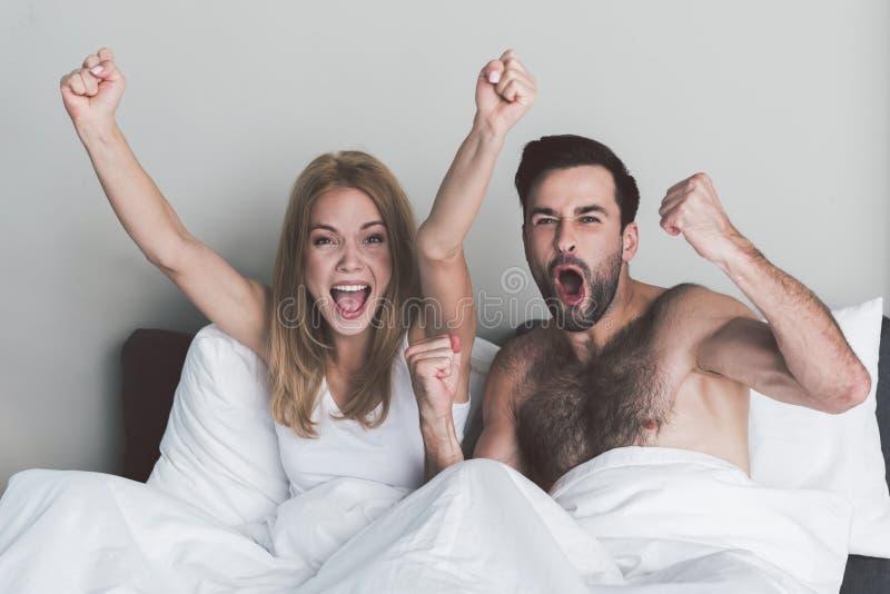 Pares entusiasmado que comemoram a vitória de sua equipe no quarto fotografia de stock royalty free