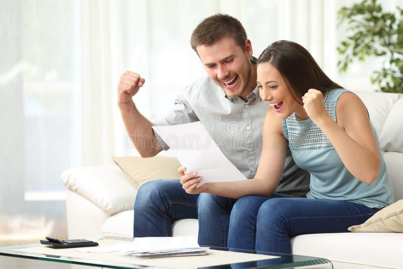 Pares entusiasmado que leem uma letra em casa imagem de stock royalty free