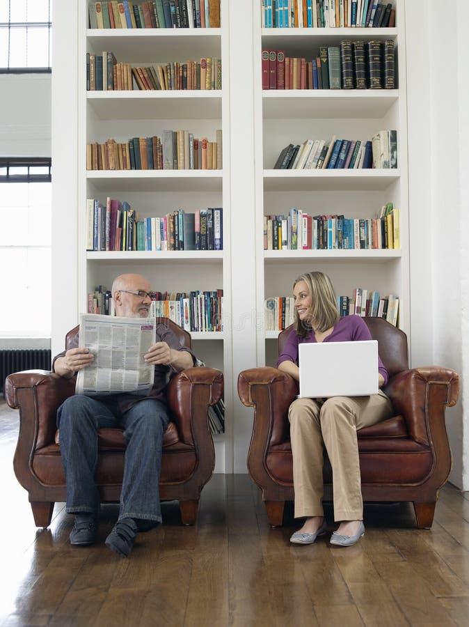 Pares envejecidos centro con el periódico y el ordenador portátil en casa fotos de archivo libres de regalías