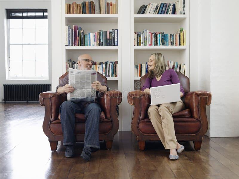 Pares envejecidos centro con el periódico y el ordenador portátil en casa fotografía de archivo