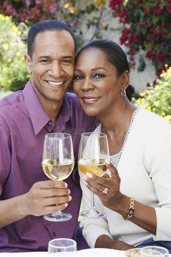 Pares envejecidos centro con las copas de vino al aire libre foto de archivo