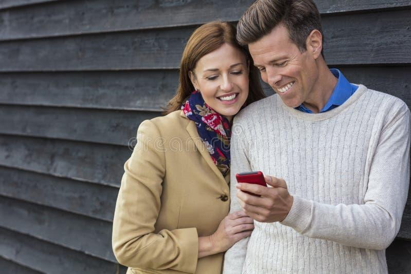 Pares envejecidos centro feliz de la mujer del hombre usando el teléfono móvil de la célula fotos de archivo libres de regalías