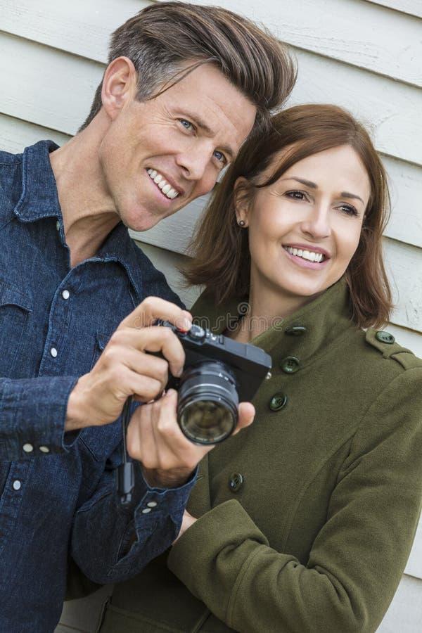 Pares envejecidos centro feliz del hombre y de la mujer usando cámara imágenes de archivo libres de regalías