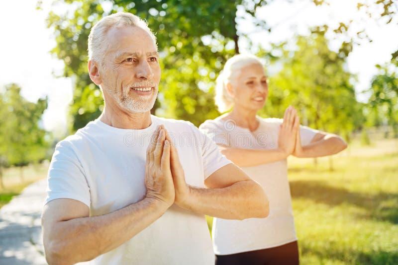 Pares envejecidos deportivos positivos que meditan en el parque foto de archivo libre de regalías