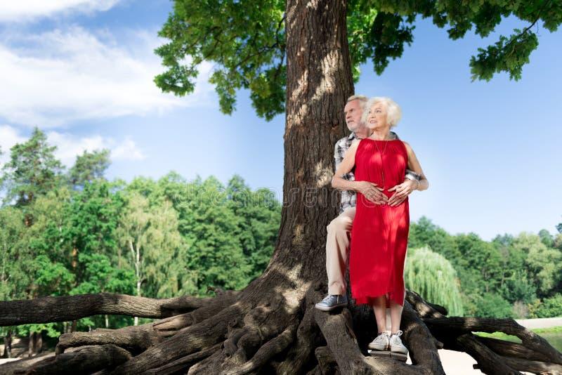 Pares envejecidos elegantes que tienen fecha muy romántica en naturaleza foto de archivo