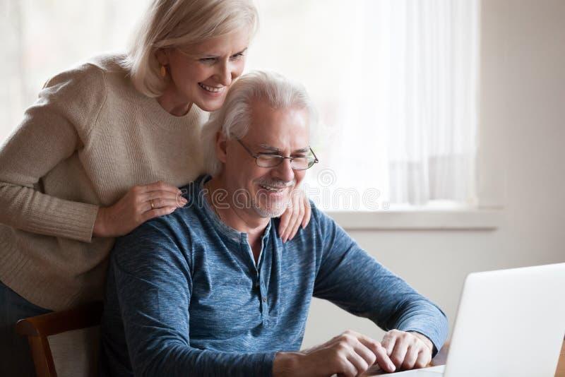 Pares envejecidos felices que miran la sonrisa de la pantalla del ordenador portátil foto de archivo