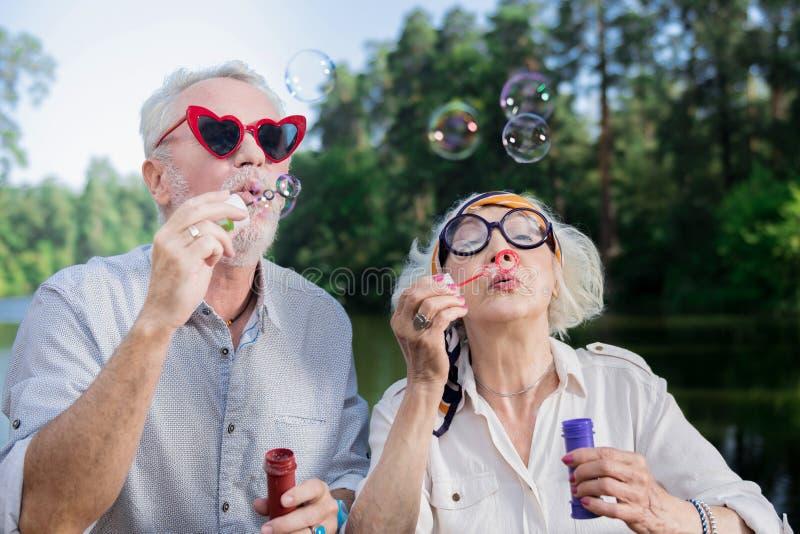 Pares envejecidos lindos que llevan los vidrios divertidos y que soplan burbujas de jabón fotos de archivo libres de regalías