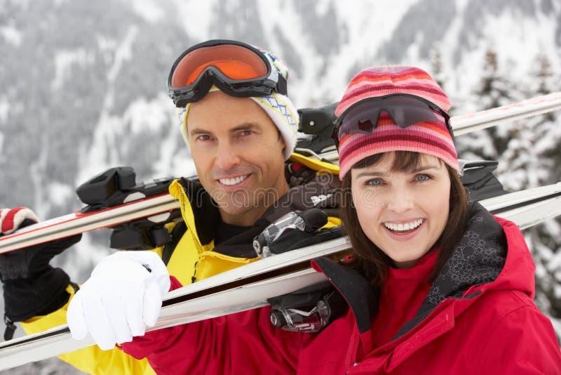 Pares envejecidos medios el día de fiesta del esquí en montañas imagen de archivo