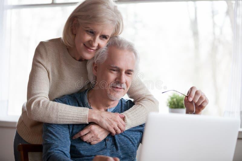 Pares envejecidos medios que miran en la pantalla de ordenador imagen de archivo