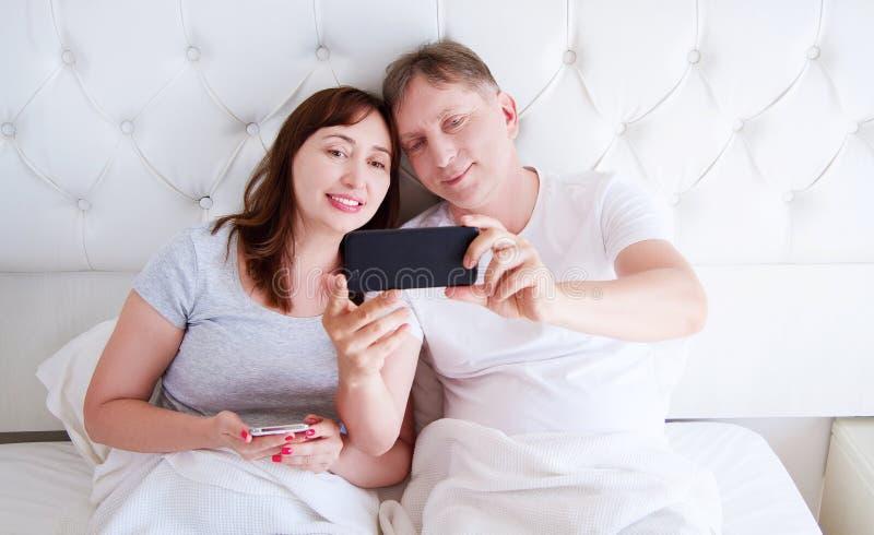 Pares envejecidos medios que sonríen y hacer el selfie o comunicar en smartphone en el dormitorio, familia feliz fotografía de archivo libre de regalías