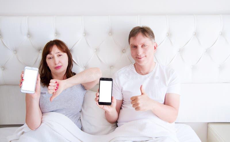 Pares envejecidos medios - teléfono del control de la mujer y muestra el mostrar de la aversión, del teléfono móvil del control d foto de archivo libre de regalías