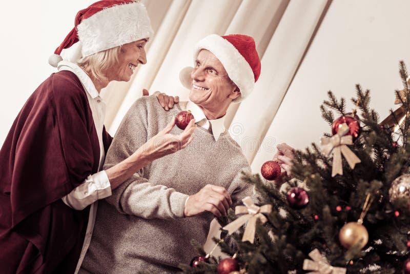 Pares envelhecidos agradáveis que estão e que decoram a árvore de Natal imagens de stock
