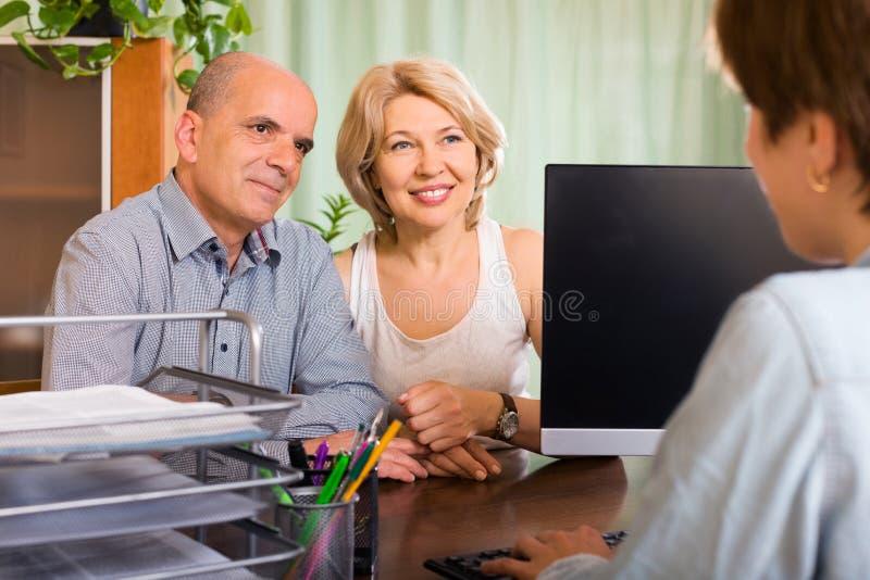 Pares envelhecidos de pensionista que falam com empregado imagens de stock