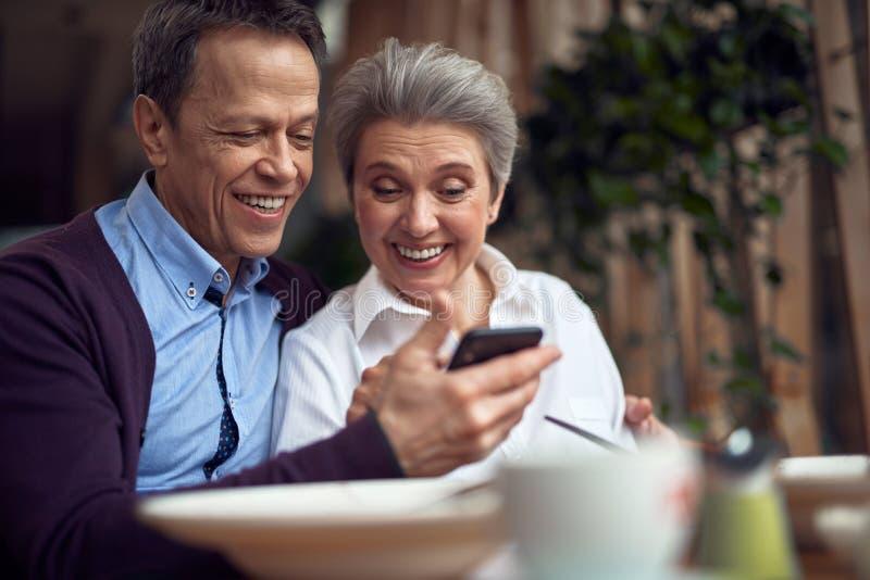 Pares envelhecidos elegantes felizes que olham o telefone celular imagens de stock