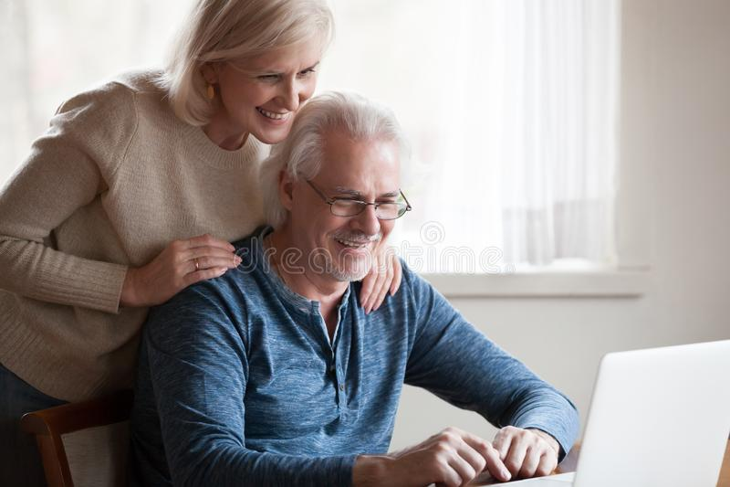 Pares envelhecidos felizes que olham o sorriso da tela do portátil foto de stock