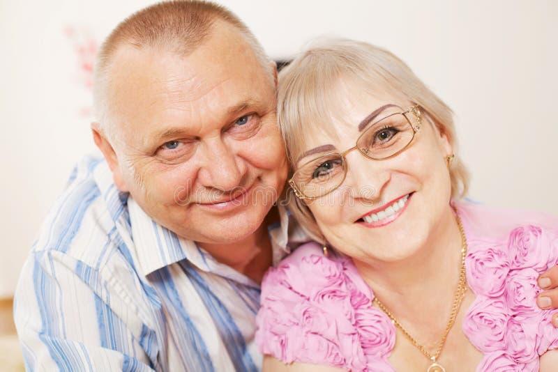 Pares envelhecidos médios felizes em casa imagens de stock royalty free