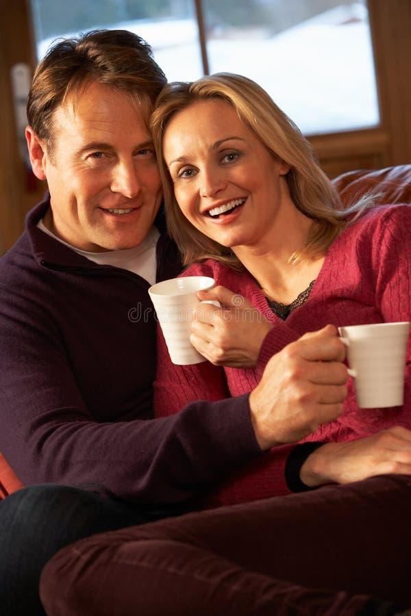 Pares envelhecidos médios que sentam-se no sofá com bebidas quentes imagens de stock