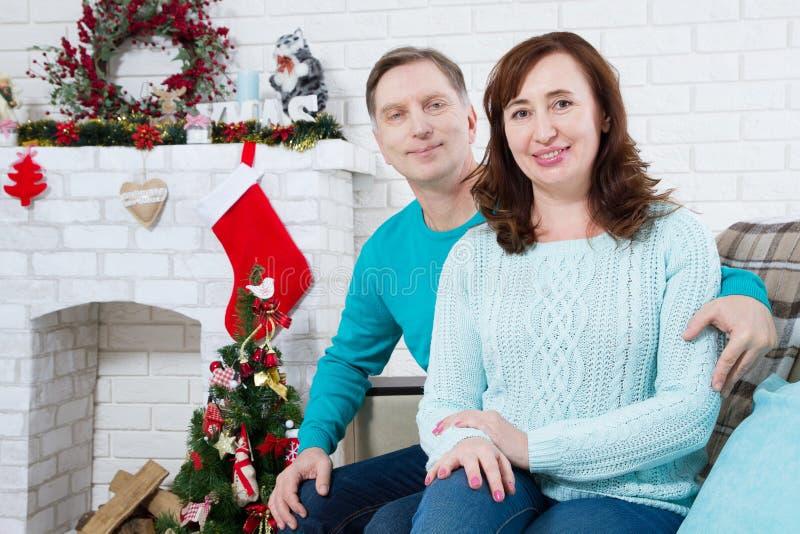 Pares envelhecidos maduros, médios felizes que sentam-se no sofá em casa Celebração do Natal, feriados do ano novo fotografia de stock royalty free