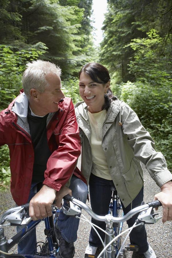 Pares envelhecidos meio com as bicicletas na floresta fotografia de stock