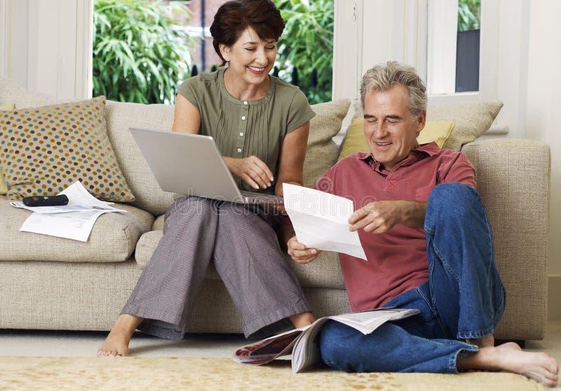 Pares envelhecidos meio com Bill And Laptop At Home fotografia de stock
