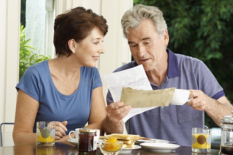 Pares envelhecidos meio com contas sobre o café da manhã imagens de stock royalty free