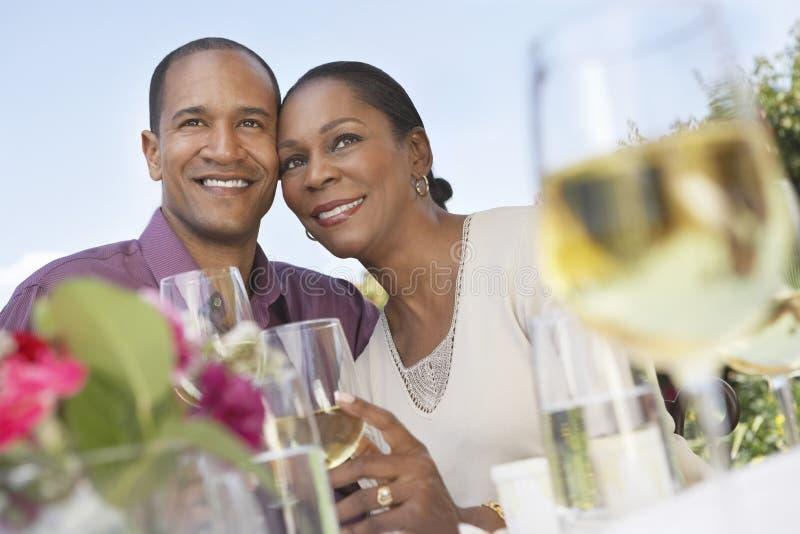 Pares envelhecidos meio com vidros de vinho fora fotografia de stock
