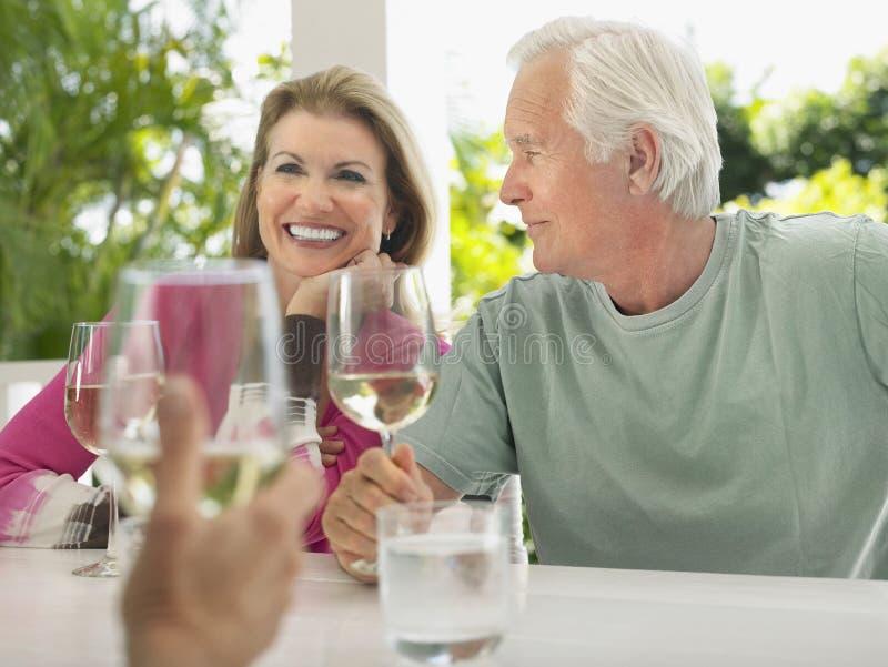 Pares envelhecidos meio que comem o vinho com amigo imagens de stock