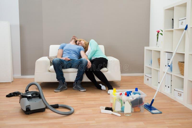 Pares esgotados no sofá na sala de visitas imagens de stock royalty free