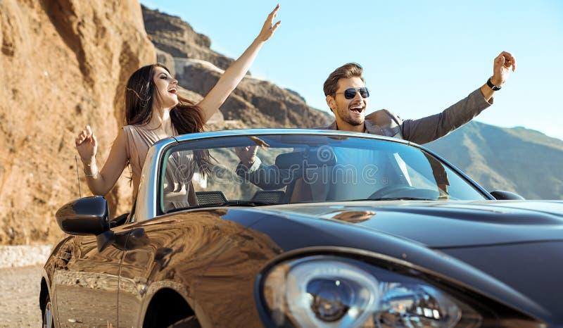 Pares espertos que montam um convertible luxuoso fotos de stock